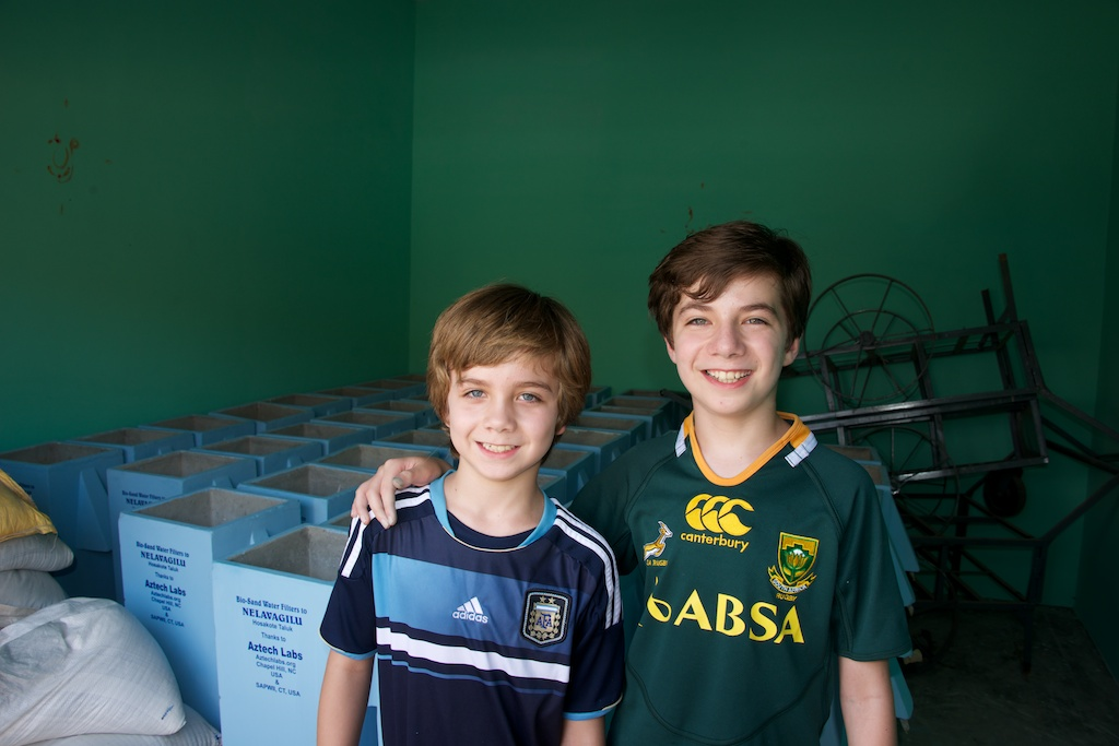 Zach and Aidan in front of 50 of the first bio-sand water filters to be donated by Aztech Labs in India.  We plan to donate a total of 1,000 filters with help from people like you.